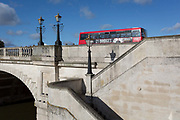 Seen from the southern bank of the river Thames is the architecture of Kingston Bridge where a London bus is driving over with an ad on the side for the film 21 Bridges, on 7th November 2019, in Kingston, London, England. A crossing has existed at Kingston since ancient times and this version of Kingston Bridge was constructed by Herbert for £26,800 and opened by the Duchess of Clarence the future Queen Adelaide on 17 July 1828. Constructed from Portland stone, it comprises of five elliptical arches.