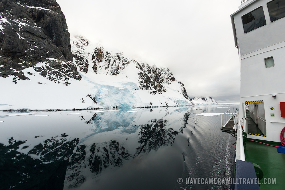 """An Antarctic cruise ship passes through glassy waters of the Lemaire Channel, as the mountains along the shore are reflected on the water. The Lemaire Channel is sometimes referred to as """"Kodak Gap"""" in a nod to its famously scenic views."""