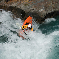 Kayaker Jeff Germain plays in waves on the  Kananaskis River in the Canadian Rockies near Calgary, Alberta.