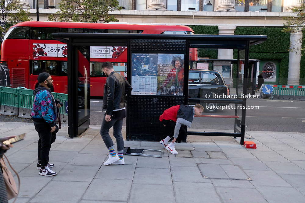 As the UK reacts to Prime Minister Boris Johnson's announcement of Lockdown 2 during the second wave of the Coronavirus pandemic, a man jumps off the roof of a bus shelter on Oxford Street, on 2nd November 2020, in London, England.