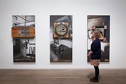 © Licensed to London News Pictures. 13/11/2012. London, UK. A Tate Modern employee looks at 'Paris Moscow' (L)(1993), 'Exorcism' (C)(1992) and 'Left, Right, Up, Down' (R)(1992) part of the NSK Embassy Moscow Interiors series by IRWIN at the press view for a new exhibition at the Tate Modern in London today (13/11/12) . The exhibition, 'A Bigger Splash: Painting After Performance', takes a look at the relationship between painting and performance, bringing together the works of over 40 artists, including Jackson Pollock and Cindy Sherman, and runs from the 14th of November 2012 to the 1st of April 2013.  Photo credit: Matt Cetti-Roberts/LNP