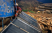 "Near piles of chopped wood logs, a local hotel owner makes adjustments to solar panels that powers his guesthouse business in a remote Himalayan village, and for the sake of passing trekkers wanting hot showers after the climb up to this altitude, on 12th December, Ghorepani, Nepal. Ghorepani is at a height of 2874m (9429 ft) and is located within the Annapurna Conservation Area (ACA), requiring a national park permit to visit and contains a number of ""guest houses"" that provide lodging and meals to mountain trekkers, many of whom spend the night before a pre-dawn trek to the top of nearby Poon Hill (3210m/10531 ft) to watch the sunrise."
