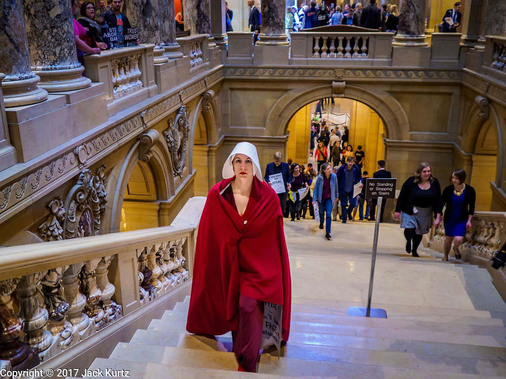 """04 MAY 2017 - ST. PAUL, MN: A woman dressed as a handmaid (from the novel and Hulu series """"A Handmaid's Tale"""") climbs the stairs to the Minnesota State Senate. About 50 people came to a protest to urge Minnesota State Senators to vote against two bills supported by the Republican party that would restrict access to women's health care in Minnesota. The protest was organized by  NARAL Pro-Choice Minnesota, NCJW Minnesota, and Planned Parenthood Minnesota. The Senate passed the bills but Minnesota's Democratic governor is expected to veto the legislation when it reaches his desk.     PHOTO BY JACK KURTZ"""