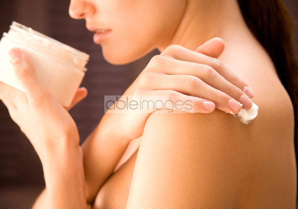 Close up of a young woman holding cream jar and  applying cream on shoulder
