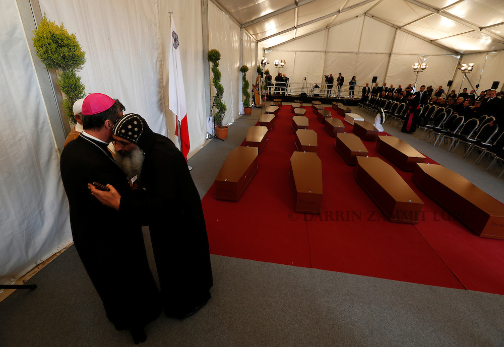 Religious leaders embrace near the coffins with the bodies of 24 migrants after an inter-faith burial service at Mater Dei Hospital in Tal-Qroqq, outside Valletta, April 23, 2015. European Union leaders who decided last year to halt the rescue of migrants trying to cross the Mediterranean will reverse their decision on Thursday at a summit hastily convened after nearly 2,000 people died at sea.  Public outrage over the deaths peaked this week after up to 900 migrants died last Sunday when their boat sank on its way to Europe from Libya.<br /> REUTERS/Darrin Zammit Lupi MALTA OUT. NO COMMERCIAL OR EDITORIAL SALES IN MALTA