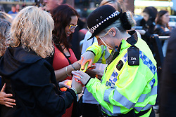 © Licensed to London News Pictures. 29/08/2015. Shoreham, UK. A police officer helps people light a candle. Thousands of people turn out at the Adur Ferry Bridge in Shoreham to light a candle at the Bridge of Light event and remember those who died in the Shoreham Air Crash last Saturday August 22nd. 11 people have been confirmed dead. Today August 29th 2015. Photo credit : Hugo Michiels/LNP