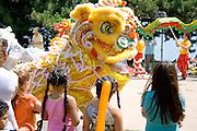 Asian dancing dragon entertaining children. Dragon Festival Lake Phalen Park St Paul Minnesota USA