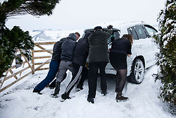 © Licensed to London News Pictures Ltd.. 01/02/2019. Bodmin Moor, UK. Staff at the Jamaica Inn help to push a car out of snow. Stranded motorists on the A30 on Bodmin Moor, who were stranded last night by heavy snowfall. Most motorists were put the up on camp beds in the nearby Jamaica Inn. Photo credit: Mark Hemsworth/LNP