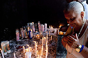 Woman paying her respects to the dead with candles. Often the lines between Candomble and Catholicism are blurred. This is especially true with the Sao Lazaro event in late January in Salvador, Bahia, Brazil, the city which is known as the home of Candomble. Sao Lazaro represents healing and the sick.