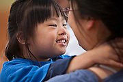 Six year old Trina Yeoh shares a tender moment with her mom Suatting Goh during the Kiwanis Club sponsored HALOS baseball game in McKinney.