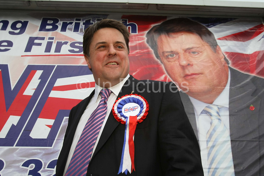 Leader of the British National Party Nick Griffin stands in front of a poster of himself during an election campaign in the constituency of Barking and Dagenham.