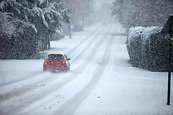 © Licensed to London News Pictures. 10/12/2017. AYLESBURY, UK.  A car drives down a snow cover street near Aylesbury. Heavy snow is causing widespread transport problems with Thames Valley Police advising drivers not to travel.  Photo credit: Cliff Hide/LNP