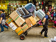08 JUNE 2018 - SEOUL, SOUTH KOREA: A porter hauls a load of merchandise through Namdaemun Market. Namdaemun Market is one of the oldest continually running markets in South Korea, and one of the largest retail markets in Seoul.[6] The streets in which the market is located were built in a time when cars were not prevalent, so the market itself is not accessible by car. The main methods of transporting goods into and out of the market are by motorcycle and hand-drawn carts. It occupies many city blocks, which are blocked off from most car traffic due to the prevalence of parking congestion in the area.       PHOTO BY JACK KURTZ