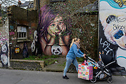 Amother pushes her child's buggy past graffiti and urban artwork that features pandas and a child's face, on 20th January 2020, in Croydon, London, England.