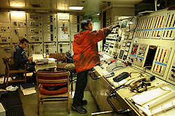 Workers attend to duties inside the engine control room aboard the Alfa K, a Mediterranean based bulk carrier with a Panamanian flag, which was undergoing repairs at the port of Piraeus in Greece on Feb. 20, 2008. Inspectors impose ITF-standard treaties on ship-owners to guarantee minimal standard working conditions for seafarers. They are on call 24 hours a day to address concerns from workers coming to port on the international ships.