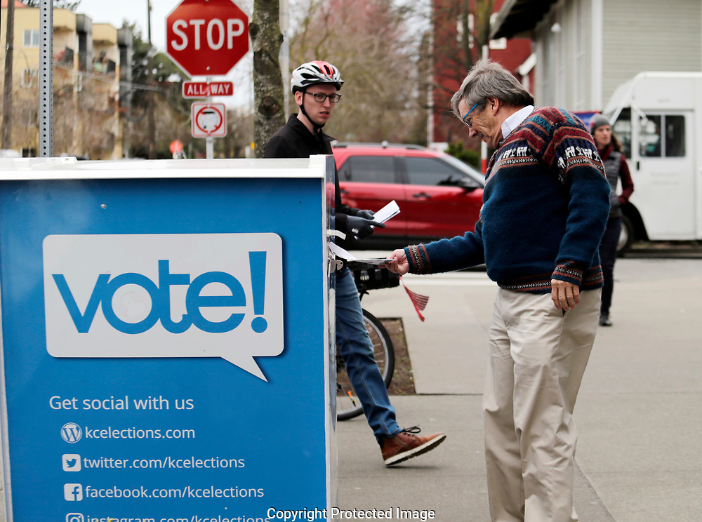 Voters drop off ballots in the Washington State primary, Tuesday, March 10, 2020 in Seattle. Washington is a vote by mail state. (AP Photo/John Froschauer)