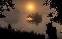 © Licensed to London News Pictures. 22/09/2021. London, UK. People watch and photograph the sun rise over a misty Pen Ponds in Richmond Park on the first day of autumn. Warm temperatures have heralded the start of the autumn season this week. Photo credit: Peter Macdiarmid/LNP