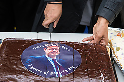 London, UK. 15 July, 2019. A cake featuring an image of Business Secretary Greg Clark is cut by catering and cleaning staff belonging to the PCS trade union and outsourced to work at the Department for Business, Energy and Industrial Strategy (BEIS) via contractors ISS World and Aramark on the picket line outside the Government department after walking out on an indefinite strike for the London Living Wage, terms and conditions comparable to the civil servants they work alongside and an end to outsourcing.