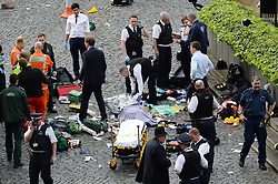 Conservative MP Tobias Ellwood (centre left, in suit) stands amongst the emergency services at the scene outside the Palace of Westminster, London, after policeman has been stabbed and his apparent attacker shot by officers in a major security incident at the Houses of Parliament.