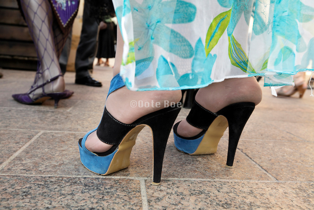 person standing with very high heeled shoes