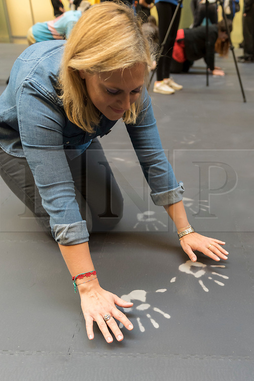"""© Licensed to London News Pictures. 01/10/2018. LONDON, UK. A visitor leaves hand prints on the heat-sensitive floor. Unveiling of the this year's Hyundai Commission by Cuban artist and activist Tania Bruguera at Tate Modern.  The work is called """"an ever-increasing figure"""", which represents the scale of mass migration and the risks involved.  Visitors are invited to interact with the work which comprises a heat-sensitive floor, which includes a portrait of a person's face beneath, combined with low frequency sounds.  The work is on display 2 October to 24 February 2019..  Photo credit: Stephen Chung/LNP"""