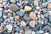 Pink granite rocks and pebbles in pastel and coral shades of colour on beach on Isle of Iona in the Inner Hebrides and Western Isles, Scotland