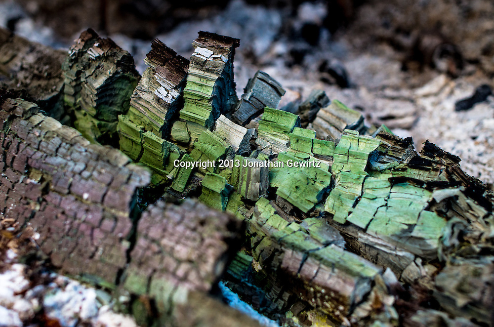 The colorful ashes of a treated piece of wood burned in a campfire. WATERMARKS WILL NOT APPEAR ON PRINTS OR LICENSED IMAGES.