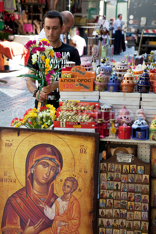 """Shop owner preparing his plastic flowers next to a shop selling religious icons, paintings and pictures in the area of Monastiraki. Among religions in Greece, the largest denomination is the Greek Orthodox Church, which represents the majority of the population and which is constitutionally recognised as the """"prevailing religion"""" of Greece (making it one of the few European countries with a state religion). Other major religions include Catholicism, Islam and Protestantism. According to a 2005 Eurobarometer Poll, 81% of Greek citizens believe that there is a God, whereas 16% believed in some sort of spirit or life force and 3% responded that they did not believe there is any sort of God, spirit or life force. Athens is the capital and largest city of Greece. It dominates the Attica periphery and is one of the world's oldest cities, as its recorded history spans around 3,400 years. Classical Athens was a powerful city-state. A centre for the arts, learning and philosophy."""