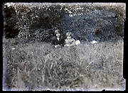 two children sitting in the grass circa 1920s