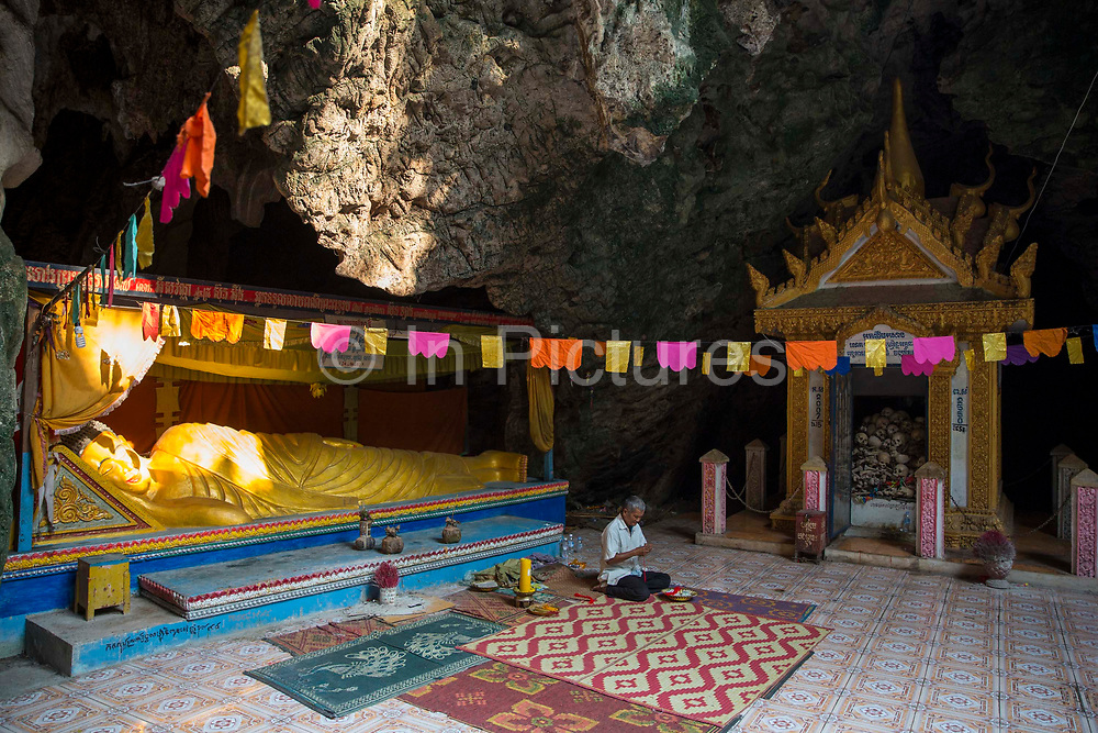 A golden reclining Buddha statue in the sunlight in a Killing Cave of Phnom Sampeau in Battambang region, Cambodia, South East Asia.  Next to the statue is a shrine containing skulls and bones from some of the victims who were killed thrown into these caves during the Khmer Rouge in 1970s. A Cambodian man sits in front of the statue making wrist band souvenirs.