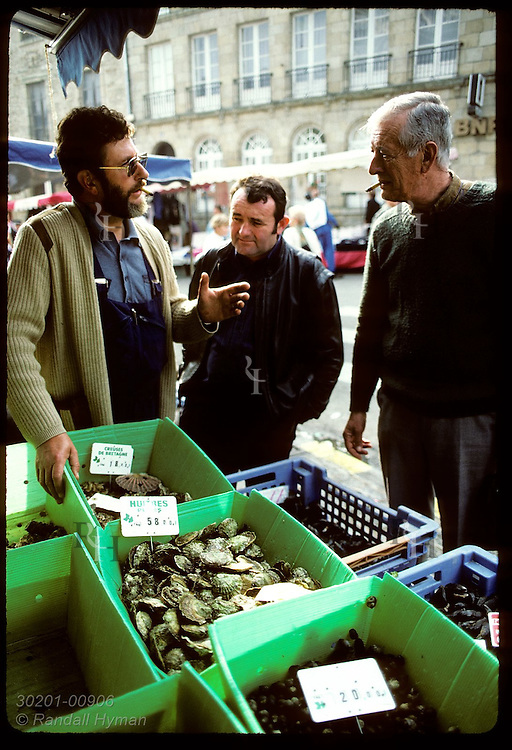 Louis Germain, seafood vendor, chats w/ friends over bins of Japanese & flat oysters; Auray. France