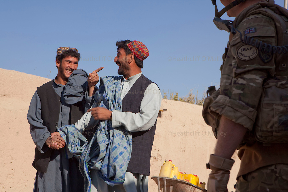 Mcc0027461 . Daily Telegraph..L Cpl Whiltshire from the FSG (Fire Support Group)B Coy, 3 Para makes two local Afghans laugh whilst on patrol in Chah e Anjir area , northern Nad e Ali...Helmand 25 November 2010