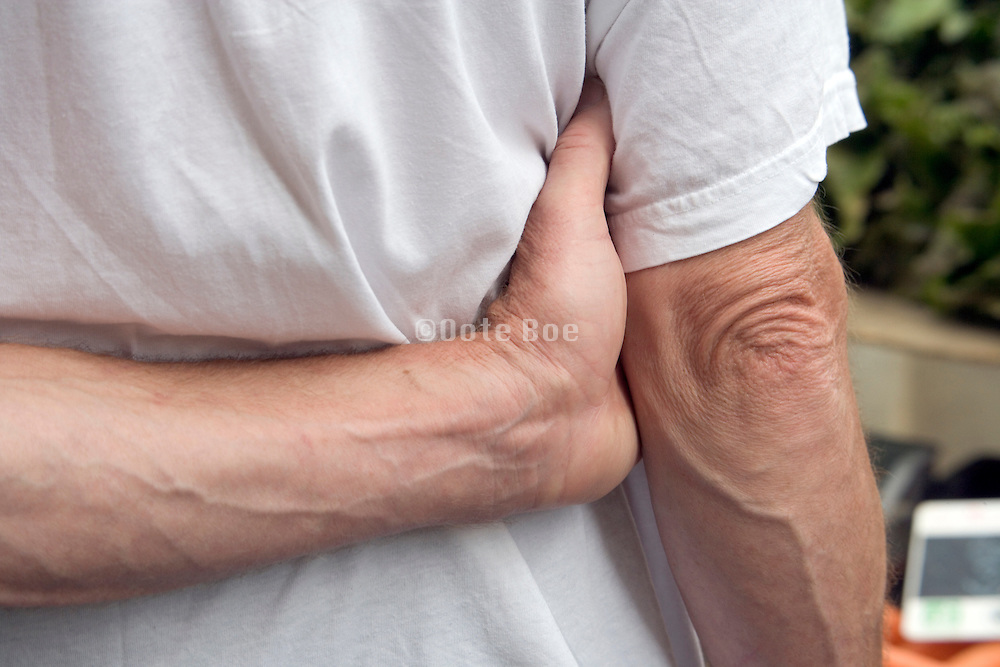 person holding his arm behind his back while waiting in line