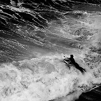 A surfer lunges over turbulent shore break at Bells Beach, Australia.
