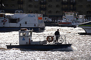 A small boat carries a cyclist and his bike as it travels on the river Thames, on 20th October 2021, in London, England.