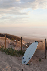 Upside down surfboard leaning against fence during sunset, Lit-et-Mixe, Aquitaine, France