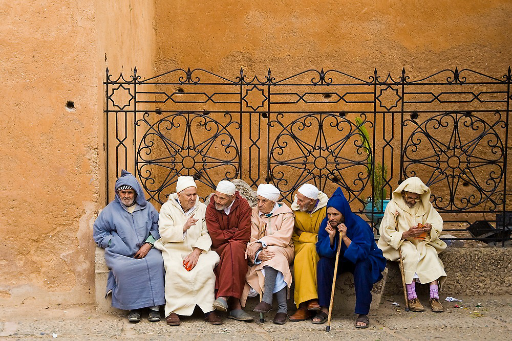 A group of Moroccan men sit and talk to each other at the entrance of the kasbah on the Uta el-Hammam square in Chefchaouen, Morocco.