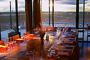 In the restaurant, a table set for dinner and a view over the vineyard. Bodega NQN Winery, Vinedos de la Patagonia, Neuquen, Patagonia, Argentina, South America