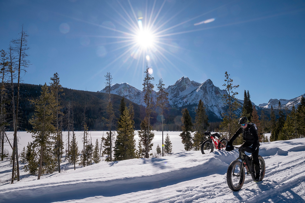 Blue sky day at Stanley Lake with McGowan Peak in the Sawtooth Mountain Range in Background and man riding a fat tire snow bike in Central Idaho.  Licensing and Open Edition Prints.