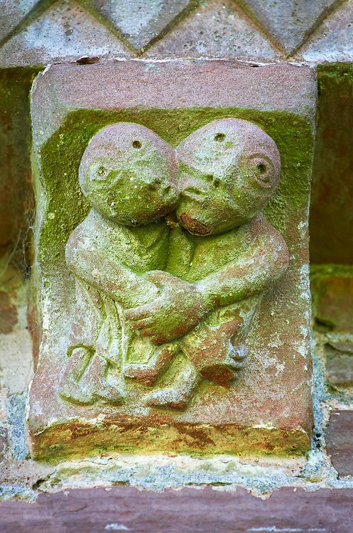 Norman Romanesque exterior corbel no 45  - sculpture of what is probably a morality tale. A man and women are grasping each other. The women seems to be clutching the mans buttocks and he has clasped her hand as if resisting. He also seems to be resisting an embrace. The Norman Romanesque Church of St Mary and St David, Kilpeck Herefordshire, England. Built around 1140 .<br /> <br /> Visit our MEDIEVAL PHOTO COLLECTIONS for more   photos  to download or buy as prints https://funkystock.photoshelter.com/gallery-collection/Medieval-Middle-Ages-Historic-Places-Arcaeological-Sites-Pictures-Images-of/C0000B5ZA54_WD0s