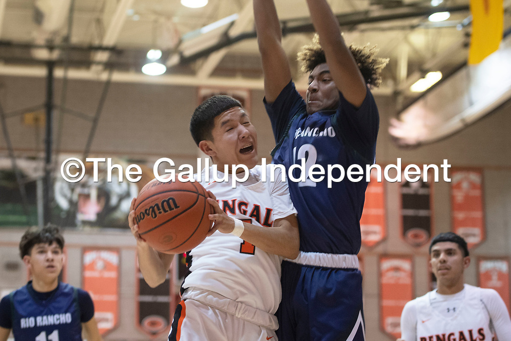 Gallup's Quentin Richards (1) drives to the basket as Rio Rancho's Lamar Bynum (12) defends at Gallup High School Tuesday night in Gallup.