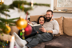 Couple lying on sofa and reading diary together