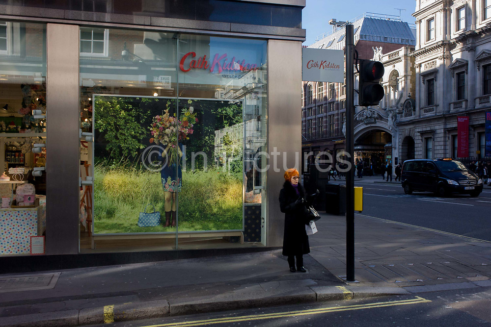A lone auburn-haired woman waits to cross the road on the corner of Duke Street, central London, outside the Piccadilly flagship branch of British fashion brand Cath Kidston. Standing still and echoed in the model featured on a large window poster on the left, she appears in a patch of winter sunlight. In the background is the entrance to Burlington's Arcade. Cath Kidston Limited is an international chain of home furnishing retail stores based in England, opened in 1993. Designer Cath Kidston opened her first shop in London's Holland Park in 1994, selling hand-embroidered tea-towels and brightly renovated furniture. In 2010, Cath Kidston sold a majority stake of the company to private equity investors TA Associates