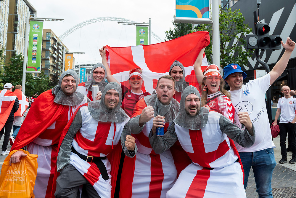© Licensed to London News Pictures. 07/07/2021. LONDON, UK.  England fans in costume arrive (and a pair of Denmark fans) outside Wembley Stadium ahead of the Euro 2020 semi-final between England and Denmark.  60,000 supporters, the most to watch a game since the pandemic began, will be in the stands as the UK government eased restrictions.  Photo credit: Stephen Chung/LNP