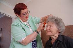 Carer combing elderly woman's hair,
