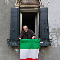 VENICE, ITALY - MARCH 16: A man hangs an Italian National Flags outside his window ahead of the celebrations for the 150th anniversary of Italy's unification on March 16, 2011 in Venice, Italy. March 17th has been declared National Festivity and events to celebrate the 150th anniversary will run in several Italian cities until the end of the year.