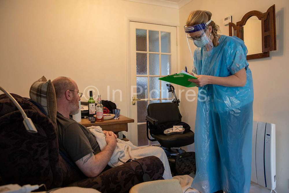 As part of a home visiting service for housebound patients Dr Fordham of the Channel Health Alliance dressed in the appropriate PPE does an assessment on a patient at their home in the community outside Dover to administer the COVID-19 Vaccination on the 27th of February 2021, Dover, Kent, United Kingdom.