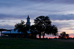 Stock photo of the silhouette of the Art Methodist Church building at sunset in Art Texas