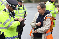 © Licensed to London News Pictures. 01/10/2021. London, UK. A protestor being arrested. Climate protest group Insulate Britain block the M1 at the junction with the North Circular at Staples Corner in North London. Insulate Britain have successfully blocked various roads around the capital over a number of weeks, resulting in a court injunction banning them from going near the M25 motorway. Photo credit: London News Pictures