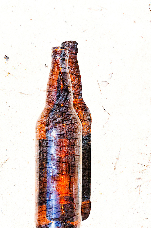 A multiple exposure photograph of a beer bottle and a stump.